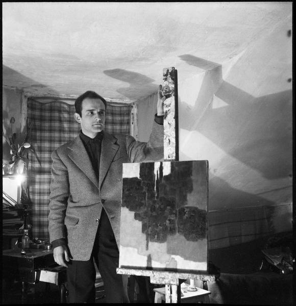 [Portrait de Paul Kallos dans son atelier à côté d'une peinture sur chevalet]