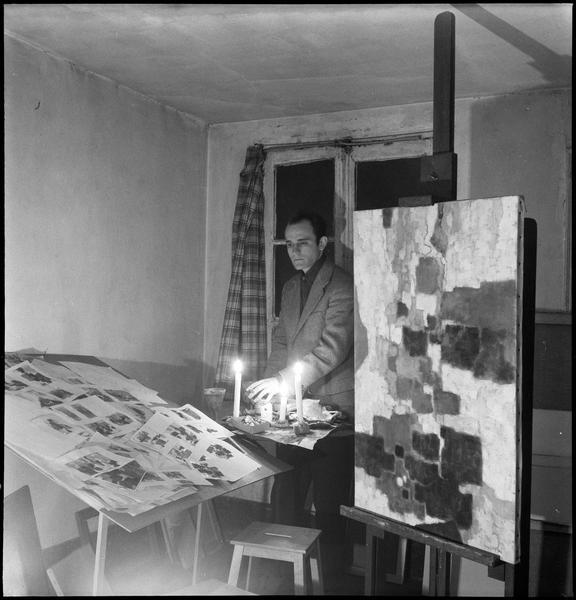 [Portrait de Paul Kallos dans son atelier avec une peinture sur chevalet au premier plan]