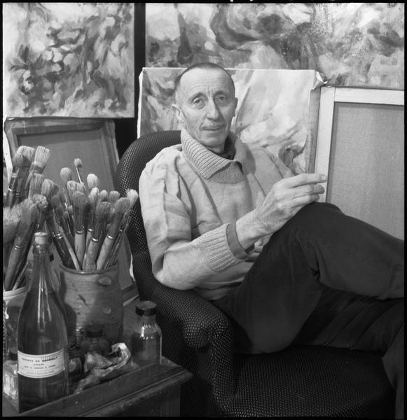 [Portrait de Jean Lombard assis dans son atelier au milieu de ses oeuvres]
