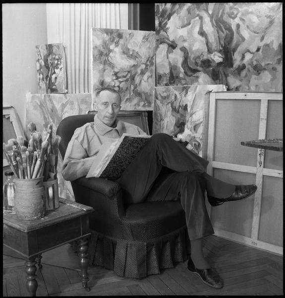 [Portrait de Jean Lombard dessinant assis dans son atelier au milieu de ses oeuvres]