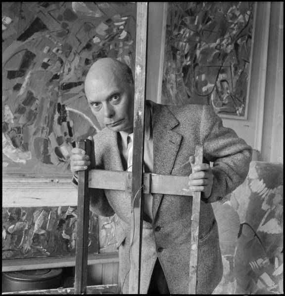 [Portrait d'André Lanskoy dans son atelier au milieu de ses oeuvres, tenant un chevalet]