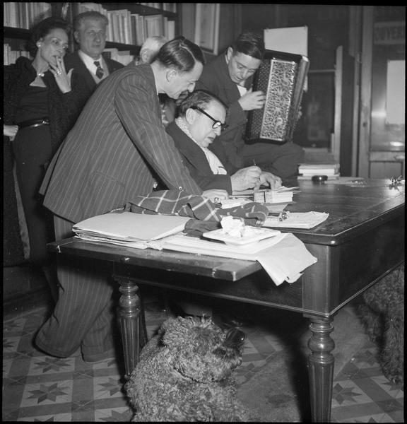 [Portrait de Richard Anacréon et l'accordéoniste V. Marceau (Marceau Verschueren) entourant Francis Carco assis au bureau]