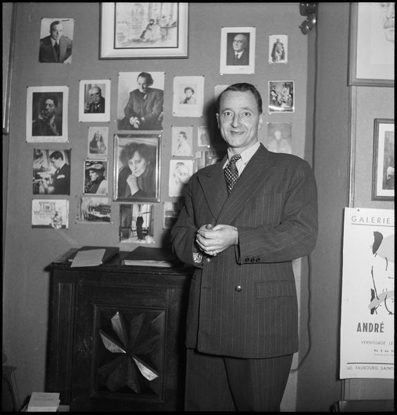 [Portrait de Richard Anacréon dans sa librairie devant un mur de photographies de ses amis]