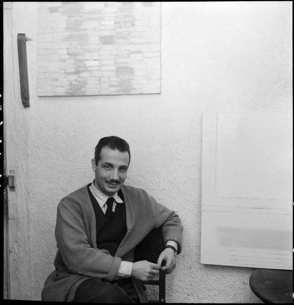 [Portrait de Constantin Macris assis dans son atelier devant ses oeuvres]