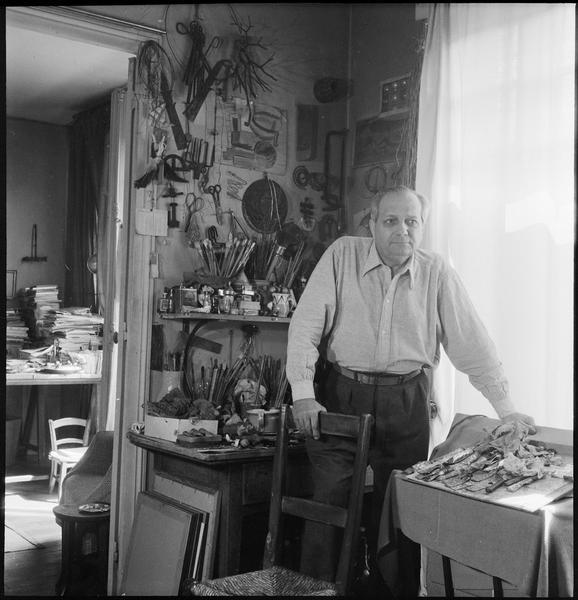 [Portrait d'Alberto Magnelli appuyé sur une chaise dans son atelier]