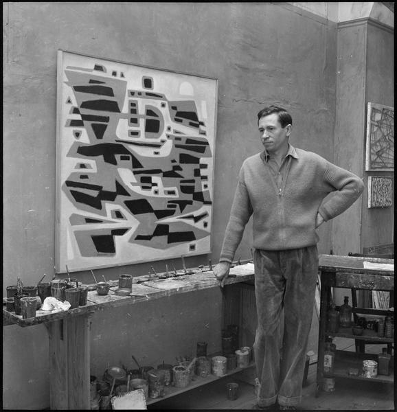 [Portrait d'Alfred Manessier dans son atelier à côté d'une oeuvre]