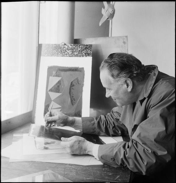 [Portrait de Marino Marini gravant une plaque attablé dans son atelier]