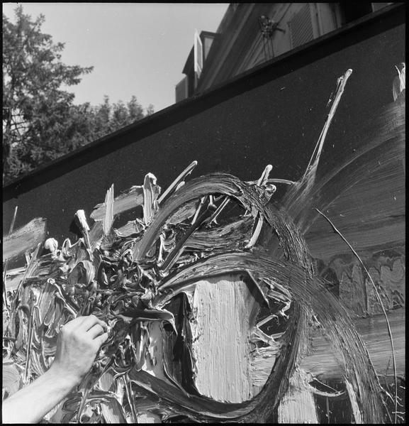 [Détail de la main de Georges Mathieu peignant dans un jardin directement avec un tube de peinture]