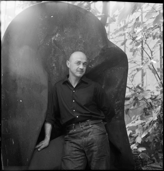 [Portrait de Robert Müller dans le jardin de son atelier appuyé sur une oeuvre]