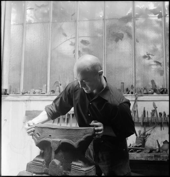 [Portrait de Robert Müller dans son atelier manipulant une pièce en fonte]