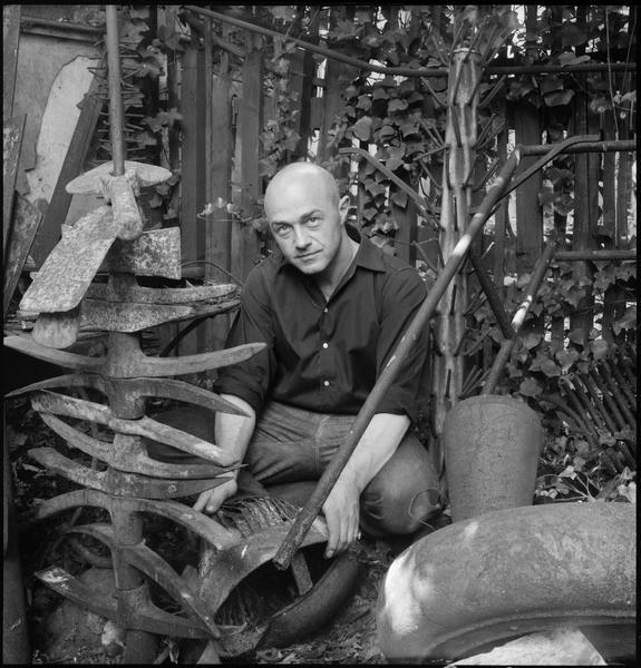 [Portrait de Robert Müller accroupi dans le jardin de son atelier entouré de pièces en fonte et métal]