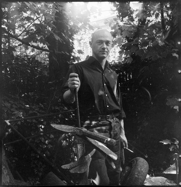 [Portrait de Robert Müller dans le jardin de son atelier entouré de pièces en fonte et métal]