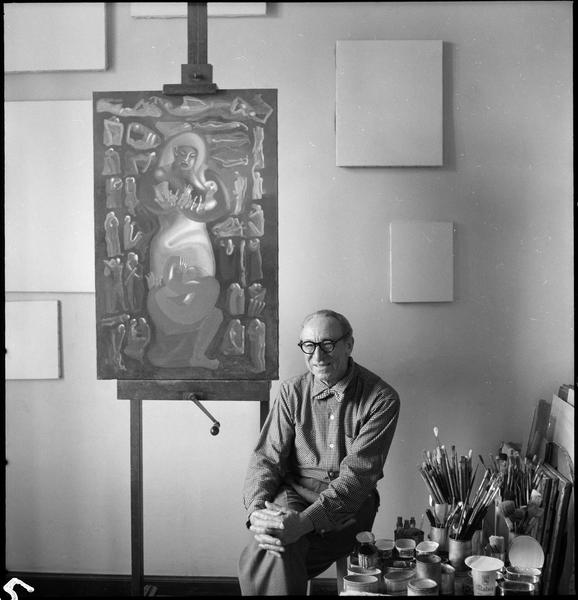 [Portrait d'Amédée Ozenfant assis dans son atelier à côté de l'une de ses oeuvres]