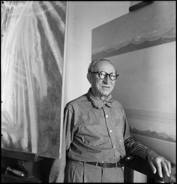 [Portrait d'Amédée Ozenfant dans son atelier à côté de ses oeuvres]