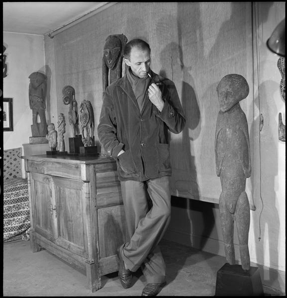 [Portrait de Pierre Loeb à côté de sculptures d'art primitif]