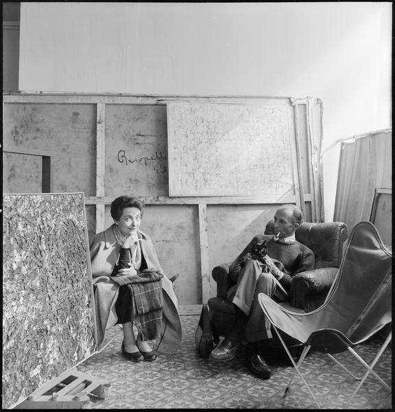 [Portrait de Maria Elena Vieira da Silva et Pierre Loeb assis dans la galerie au milieu d'oeuvres de Jean-Paul Riopelle]