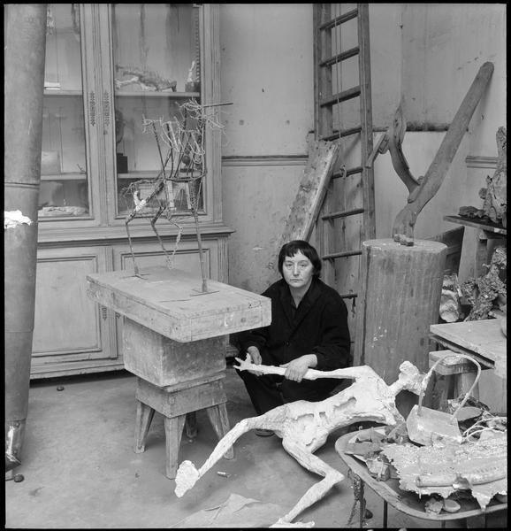 [Portrait de Germaine Richier accroupie dans son atelier à côté d'une oeuvre]