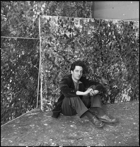 [Portrait de Jean-Paul Riopelle assis sur le sol de son atelier au milieu de ses oeuvres]