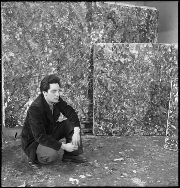 [Portrait de Jean-Paul Riopelle accroupi dans son atelier au milieu de ses oeuvres]