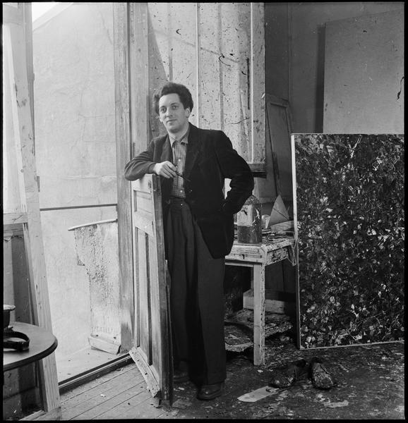 [Portrait de Jean-Paul Riopelle appuyé sur le battant d'une porte dans son atelier]