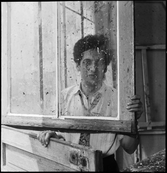 [Portrait de Jean-Paul Riopelle dans son atelier derrière la fenêtre maculée de peinture]