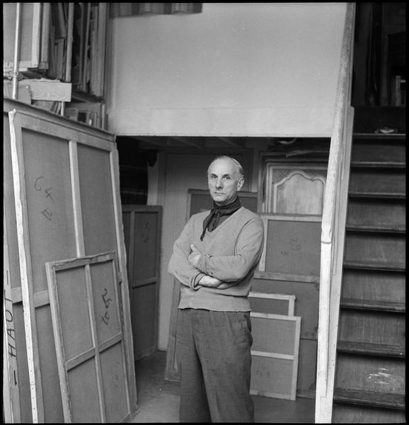 [Portrait de Gérard Schneider dans son atelier à côté de son stock de peintures]