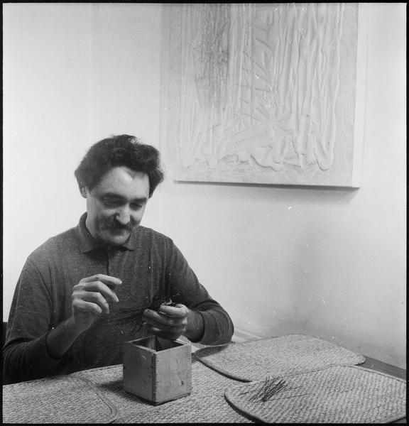 [Portrait de Jesus-Rafael Soto assis dans son atelier travaillant des tiges métalliques]
