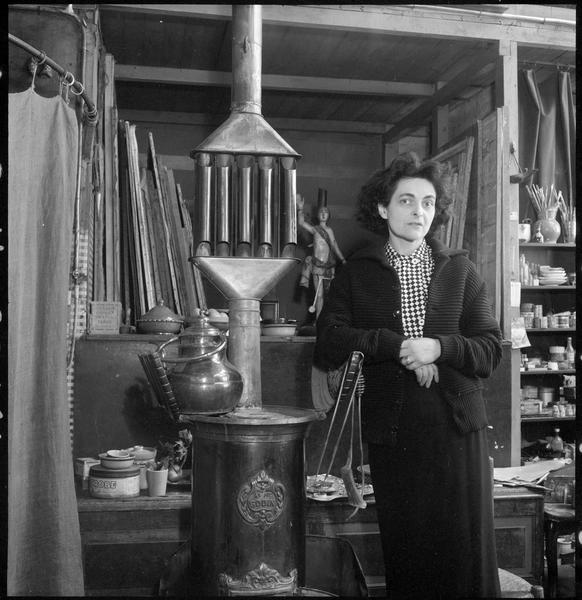 [Portrait de Maria Elena Vieira da Silva à côté d'un poêle dans son atelier]