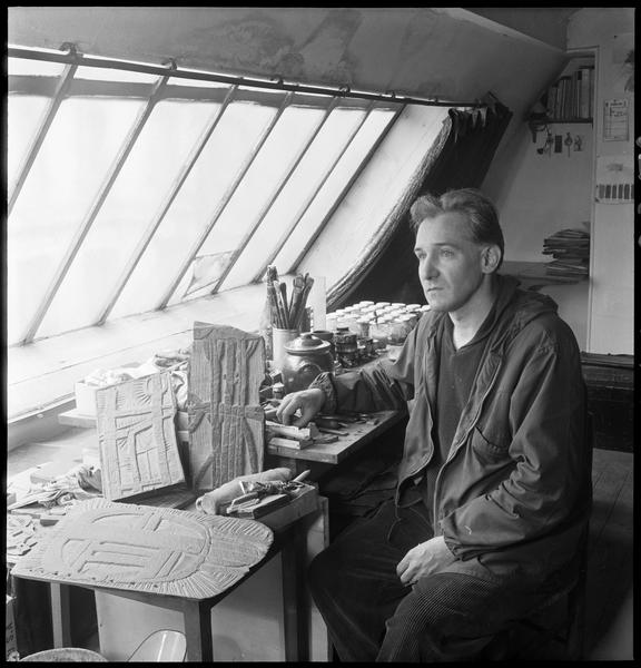 [Portrait de Raoul Ubac assis dans son atelier face à sa table de travail]