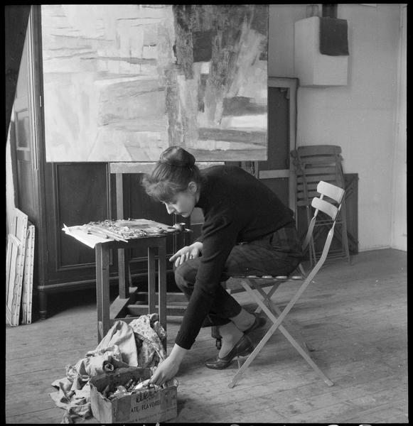 [Portrait d'Agathe Vaïto assise dans son atelier devant une peinture sur chevalet]