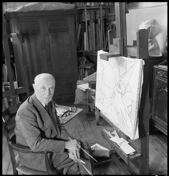 [Portrait de Jacques Villon assis dans son atelier devant une peinture sur chevalet, pinceaux dans les mains]