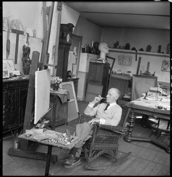 [Portrait de Jacques Villon assis dans son atelier devant une peinture sur chevalet, pinceau à la main]