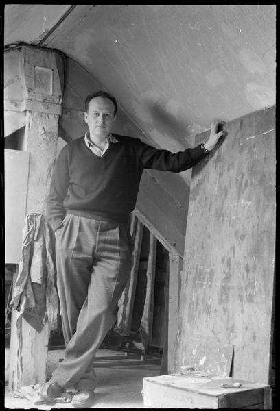 [Portrait de Jacques Germain dans son atelier appuyé sur une planche de bois]