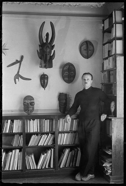 [Portrait de Charles Lapicque dans sa bibliothèque à côté de sa collection de masques africains]