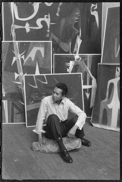 [Portrait de Wifredo Lam assis dans son atelier au milieu de ses oeuvres]
