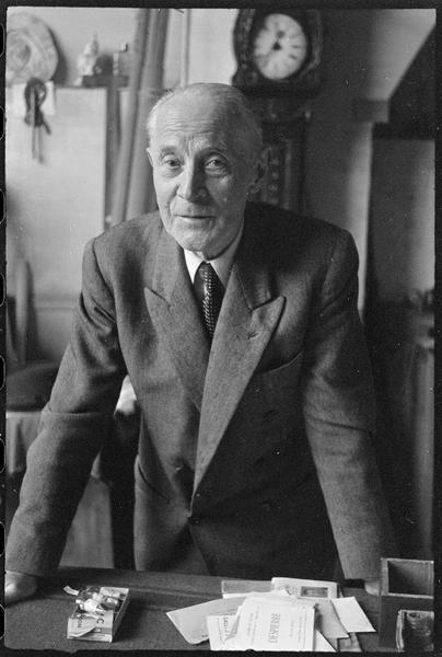 [Portrait de Jacques Villon dans son atelier appuyé contre une table]