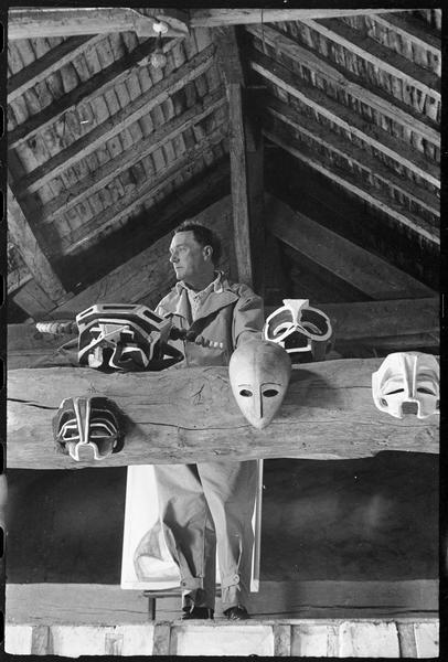 [Portrait de Henri-Georges Adam dans le grenier de son atelier avec les masques créés pour la pièce 'Les Mouches' de Jean-Paul Sartre accrochés à la poutre]