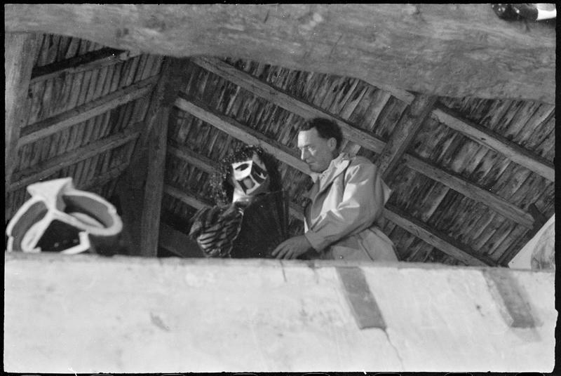 [Portrait de Henri-Georges Adam dans le grenier de son atelier avec une personne portant l'un des masques créés pour la pièce 'Les Mouches' de Jean-Paul Sartre]