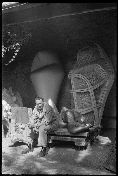 [Portrait de Henri-Georges Adam assis avec son chien dans la cour de son atelier devant ses oeuvres]