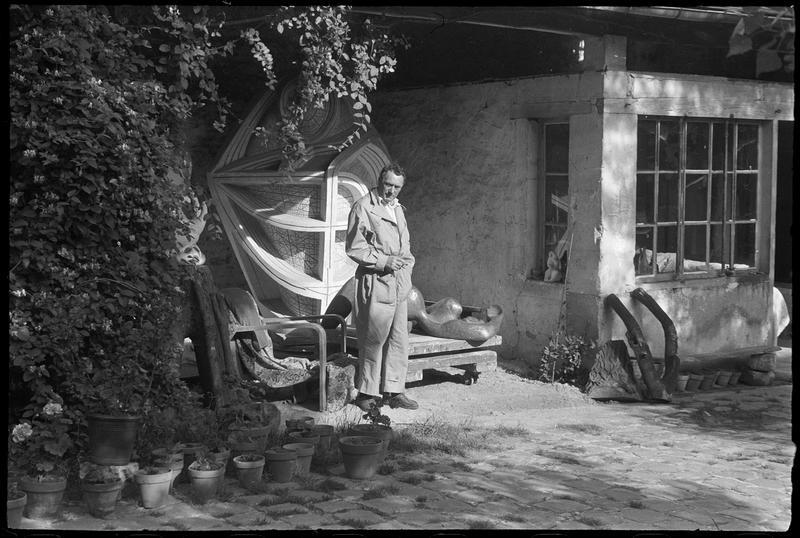 [Portrait de Henri-Georges Adam dans la cour de son atelier à côté de ses oeuvres]
