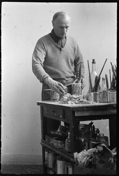 [Portrait de Gérard Schneider dans son atelier derrière sa table de travail]