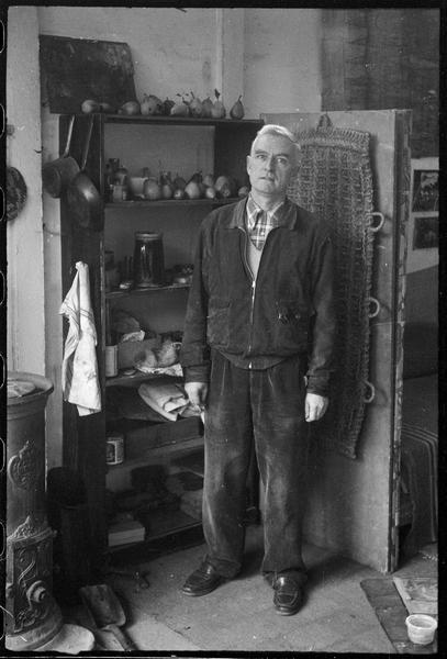 [Portrait de Jean Bazaine dans son atelier à côté d'un poêle]