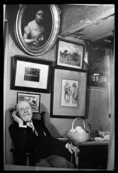 [Portrait de Henri Hamm tendant l'oreille assis dans une pièce décorée de cadres]