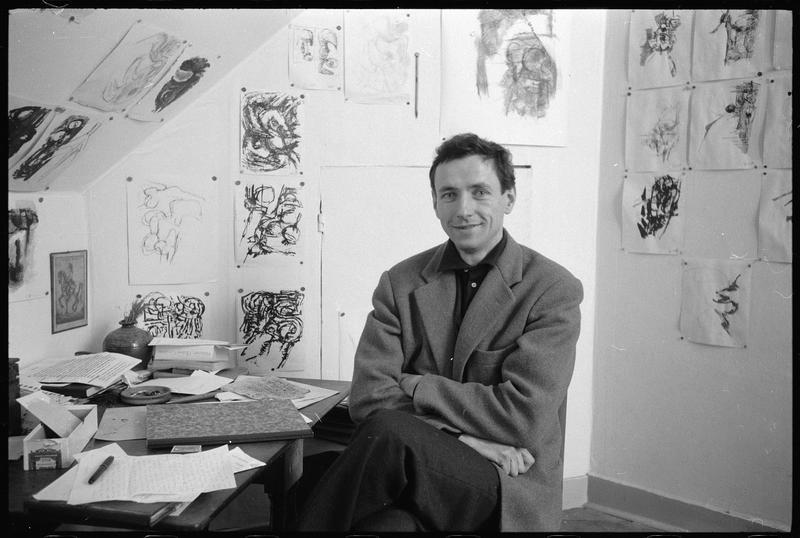 [Portrait de Bernard Dufour assis dans le bureau de son atelier dont les murs sont couverts de dessins]