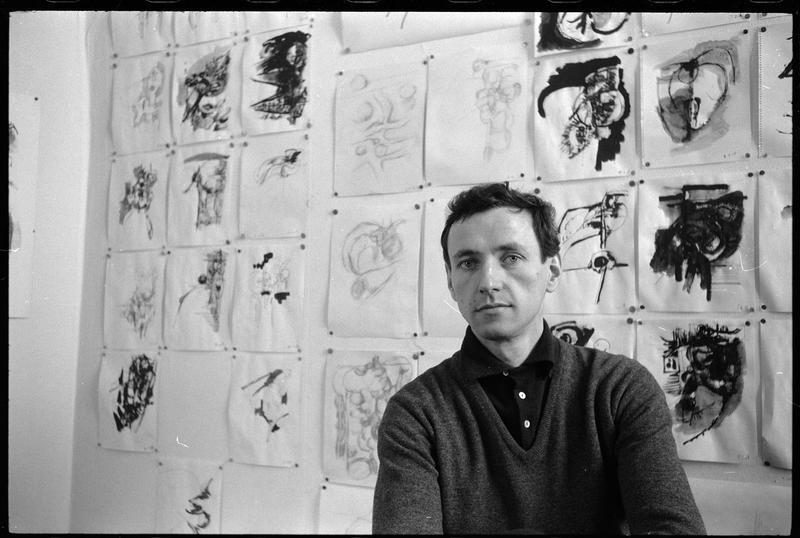 [Portrait de Bernard Dufour assis dans le bureau de son atelier face à un mur couvert de dessins]