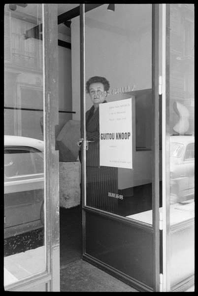 [Exposition de Guitou Knoop, juin à juillet 1958 : Guitou Knoop derrière la porte de la galerie]