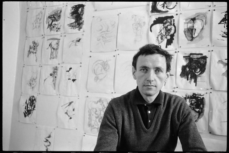 [Portrait de Bernard Dufour dans le bureau de son atelier face à un mur couvert de dessins]