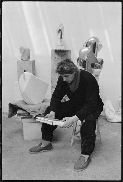 [Portrait d'Emile Gilioli assis dans son atelier au milieu de ses oeuvres, tenant dans les mains un livre d'art]
