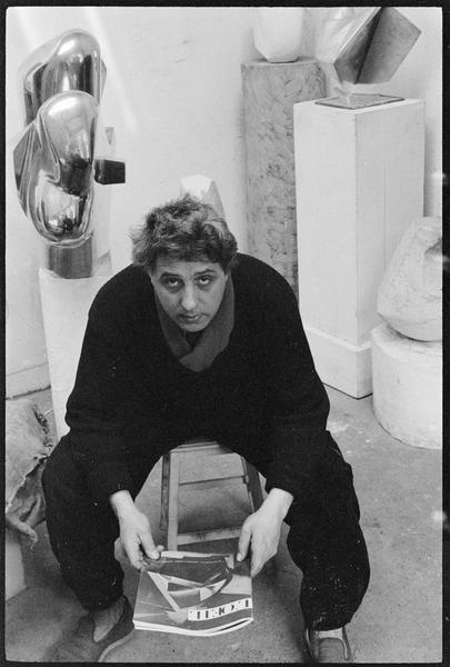 [Portrait d'Emile Gilioli assis dans son atelier au milieu de ses oeuvres, tenant dans les mains le magazine L'Oeil]