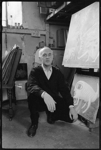 [Portrait de Victor Brauner accroupi dans son atelier à côté de deux peintures, dont 'La rencontre du 2 bis Perrel' (hommage au Douanier Rousseau)]